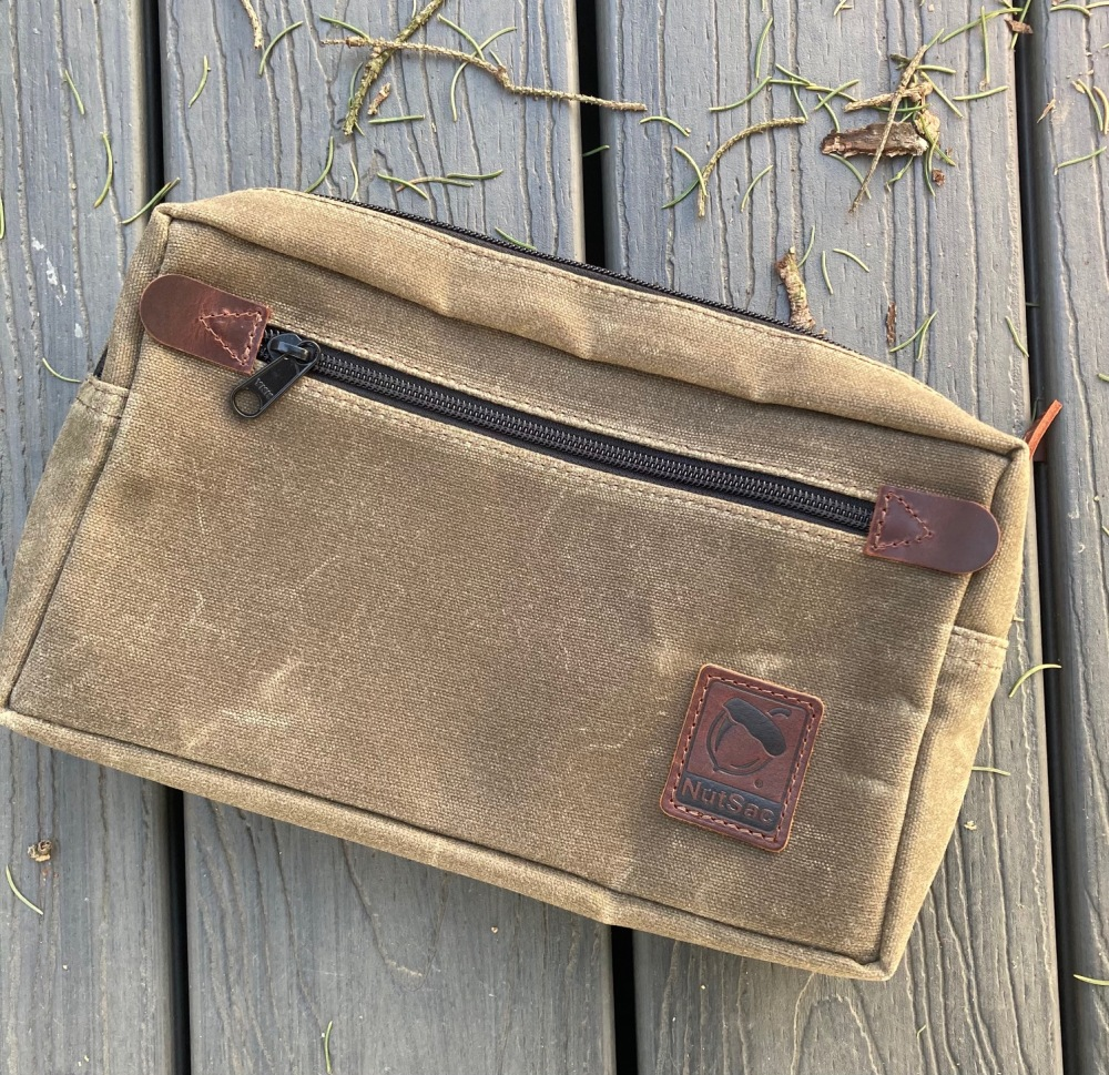 The Man-Bag, Dammit (MBD) from Nutsac in the waxed tan canvas color. Featured on the front is a large zipper pocket.